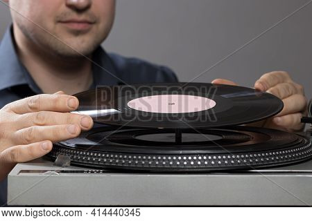 A Man And Vintage Record Player While Recording, The Record Spins And Music Plays. Gramophone And An