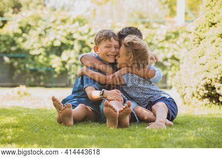 Playful Siblings Having Fun On A Green Lawn