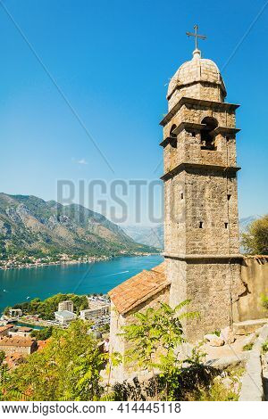 View On Church, Ancient Walls, Mountains And Sea In Kotor Old Town. Montenegro, Kotor Bay