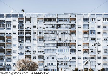 A Bluish Facade Of A Tall Big White Panel Residential House With Balconies And Windows; A Texture Of