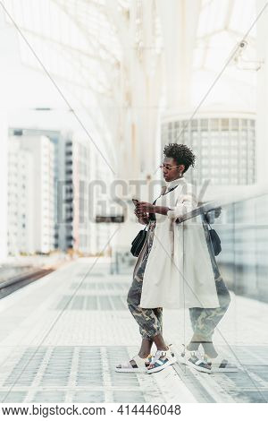 Fancy Dapper Young Black Female In Sunglasses, White Trench, And Camouflage Trousers, Is Using A Sma