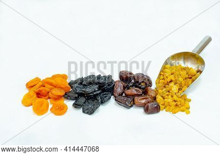 Dried Fruits - Dates, Dried Apricots, Prunes, Raisins On A White Background, With An Iron Spatula