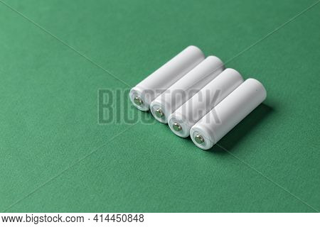 Rechargeable Aaa Batteries In White On A Green Background. Place For Text. Green Energy Concept.