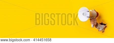 Hand Holds A Megaphone From A Hole In The Wall On A Yellow Background. Concept Of Hiring, Advertisin