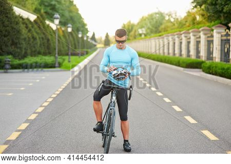 Full Length Shot Of Focused Male Cyclist Wearing Glasses, Putting On Helmet, Getting Ready For Cycli