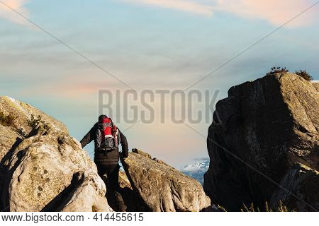 Unrecognizable Hiker From Behind With Red Backpack Walking On The Rocks Of A Mountain At Sunset. Mou