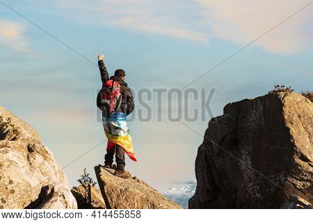 Hiker Standing On A Rock In The Mountain, Raising His Fist And Carrying A Rainbow Flag Of Peace. Spo