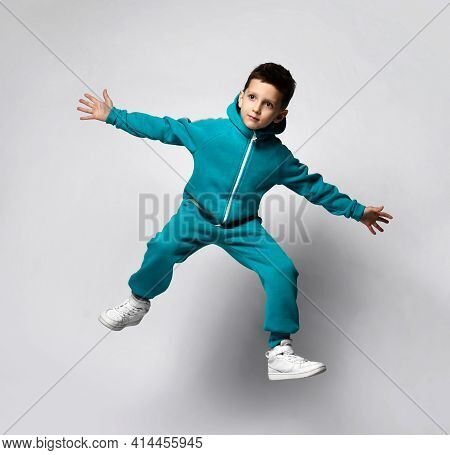 Fashion Boy Child In Trendy Warm Tracksuit Suit Jumping Up Isolated On Studio Background. School Kid