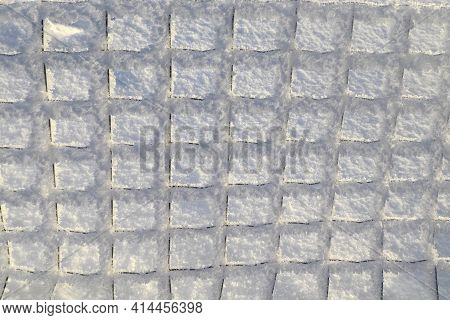 A Mesh Fence With A Pattern Of Small Squares Covered With Hoarfrost On A Background Of Snow. Winter