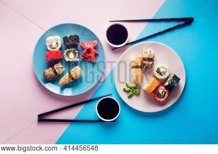 Tasty Sushi Rolls Set On Blue Plate  With Sauces, Chopsticks, Ginger And Wasabi On Colored Backgroun