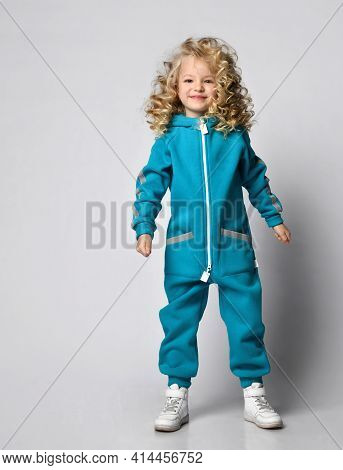 Smiling Girl In Warm Trendy Sportswear Posing For The Camera In A Studio Portrait. Attractive Beauty