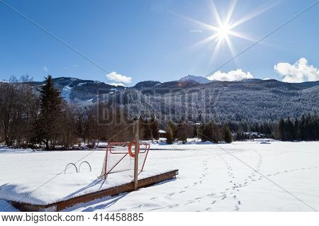 Frozen Mountain Lake With A Sunburst On A Sunny Day.