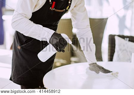 Male Waiter In Black Apron, Medical Mask And Gloves Cleaning White Table At The Restaurant By Disinf