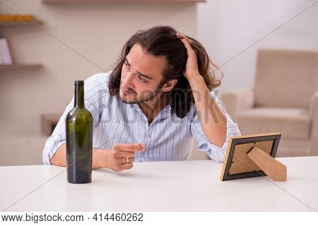 Young man drinking alcohol at home in unhappy love concept