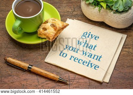 give what you want to receive inspirational handwriting on a napkin with a cup of coffee, relationship, compassion, generosity and personal development concept