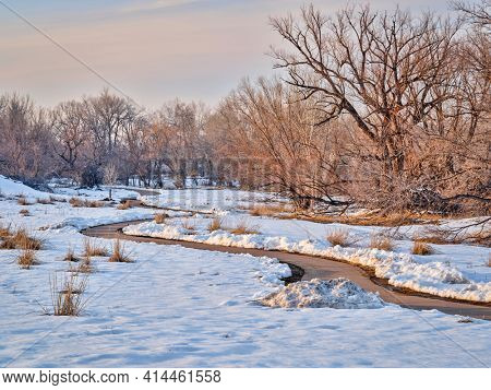 dusk over meandering  bike trail in winter scenery - one of numerous bike trails in Fort Collins, northern Colorado, recreation and commuting concept