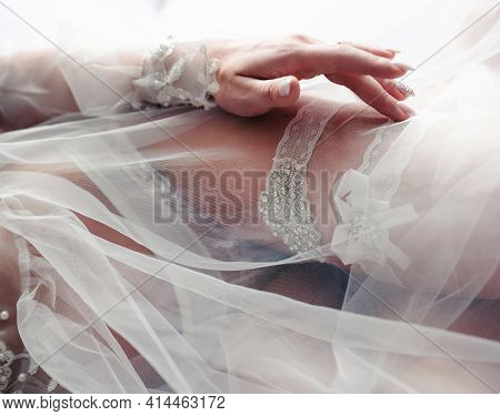 The Bride Out Of Focus In A White Negligee Wears A Garter On Her Leg. Tender Morning Of The Bride. S