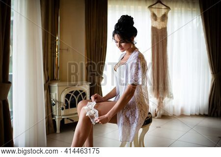 The Bride In A White Negligee Wears A Garter On Her Leg. Morning Wedding Preparations