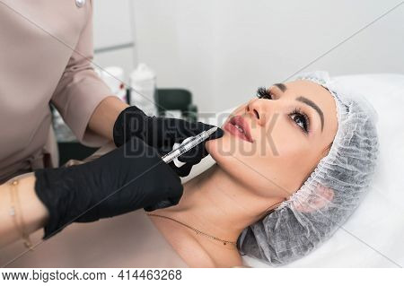 Cosmetologist Making Injection In Lips. Young Woman Gets Beauty Facial Injections In Salon. Face Rej