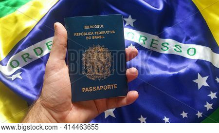 Male Hand Holding Brazilian Passport With Brazilian Flag In Background.