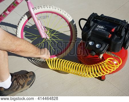 Man Inflating Childs Bicycle Tire With Air From Compressor.
