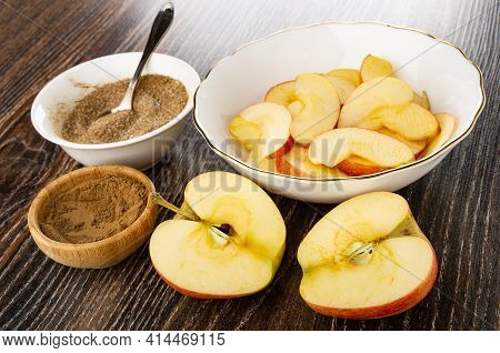 Spoon In White Bowl With Sugar And Ground Cinnamon, Slices Of Apples In Glass Bowl, Bowl With Ground