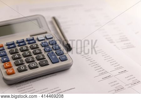Calculator And Pen Placed On Accounting Documents. Select Focus Calculator Button. Financial Busines