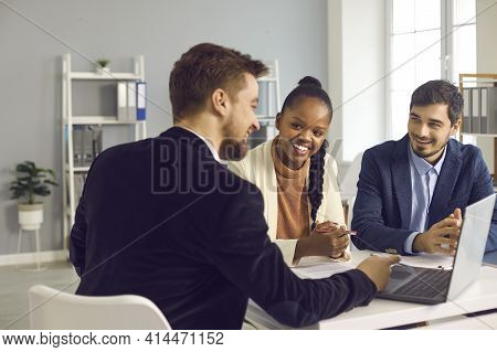 Bank Manager In The Office Consults A Caucasian Man And His African-american Wife.
