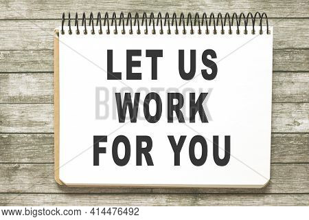 Text Let Us Work For You On Notebook Page On Wooden Table In Office Workspace. Business Concept