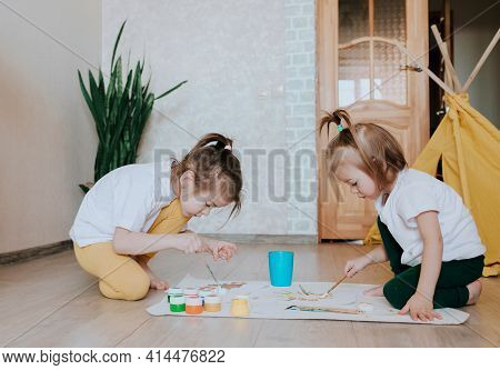 Two Girls In Light-colored Clothes Sit On The Floor On Their Knees And Enthusiastically Draw With Br