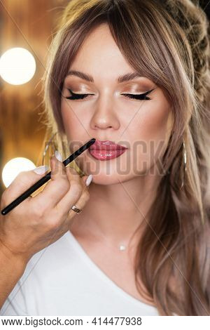 Makeup Artist Applies Lip Gloss To Plump, Sensual Lips Beautiful Woman Face. Make Up Process Details