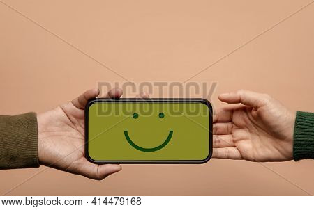 Customer Experience Concept. Happy Client Giving A Smiling Emoticon Via Mobile Phone To Brand. Feedb