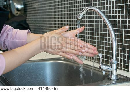 Cropped Shot View Of Woman  Washing Hands At Sink Basin Faucet In Kitchen Room. Washing Your Hands I
