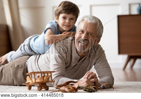 Portrait Of Happy Older Grandfather Play With Little Grandson