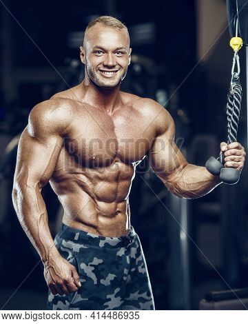 Fit Man Training Abs Muscles At Gym.