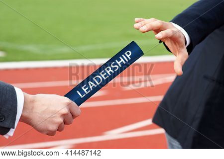 Leadership - Businessmen Hand Over Baton In Stadium Relay Race