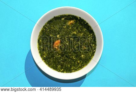 Famous Traditional Arabic Cuisine. Molokhia Soup With Shrimps On Blue Background. Flat Lay, Top View
