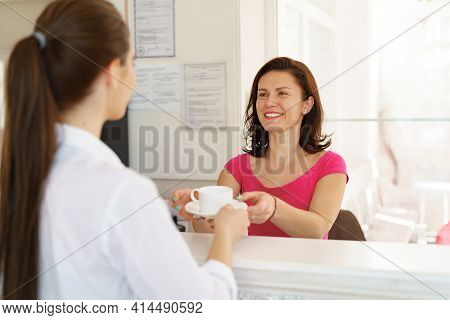 Lovely Receptionist Serving Client With A Cup Of Tea In Beauty Salon. Beautitians Consulting Her Cli