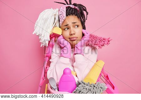 Housekeeping Concept. Sad Bored Woman With Dreadlocks Holds Chin Looks Sadly At Camera Surrounded By