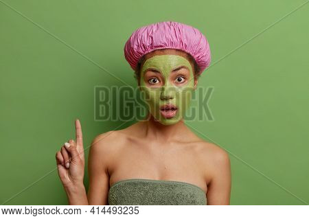 Photo Of Surprised Ethnic Woman Points Above Has Wondered Expression Applies Clay Green Facial Mask