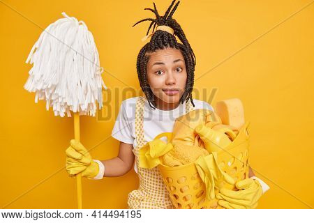 Homework Cleaning Routine Concept. Puzzed Afro American Woman With Dreadlocks Has Housekeeping Job H