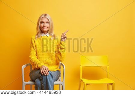Serious Middle Aged European Woman With Calm Expression Wears Jumper And Jeans Poses On Chair Indica