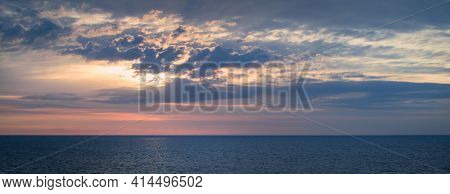 Panoramic View Of A Picturesque And Dramatic Sunrise Sky Over A Vast And Calm Ocean.