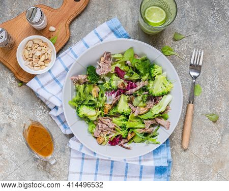 Healthy Salad With Boiled Broccoli, Duck, Fried Mushrooms And Peanut Dressing In A Gray Plate On A L
