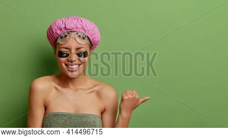 Overjoyed Dark Skinned Young Woman Points Thumb Away Feels Very Glad Closes Eyes Demonsrtrates Somet