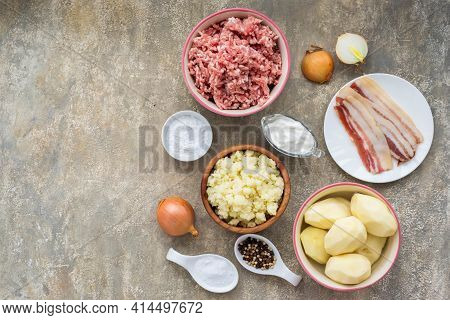 Prepared Ingredients For Cooking A Lithuanian Dish Zeppelin From Grated Potatoes On A Light Concrete
