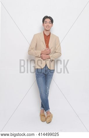 full length handsome casual man wearing suit with brown shirt with blue jeans , brown shoes  posing in studio