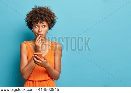Horizontal Shot Of Thoughtful African American Woman Holds Modern Smartphone In Hand Waits For Call
