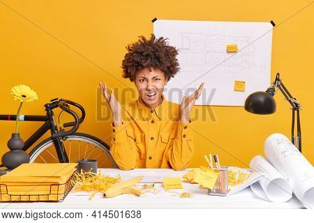 Frustrated Curly Afro American Female Office Worker Raises Palms Looks Angrily Puzzled To Make Mista
