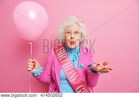 Old People And Festive Occasion Concept. Beautiful Wrinkled Woman Pensioner Keeps Lips Rounded Raise